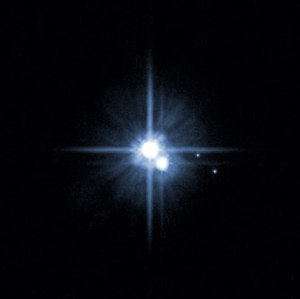 In 2005, this image from NASA's Hubble Space Telescope was used to identify two new moons orbiting Pluto. Pluto is in the center. The moon Charon is just below it. The newly discovered moons, Nix and Hydra, are to the right of Pluto and Charon. Credits: NASA, ESA, H. Weaver (JHU/APL), A. Stern (SwRI), and the HST