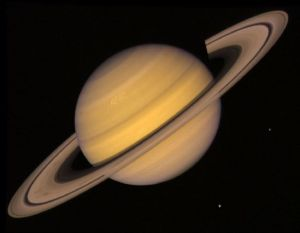 This montage of images of the Saturnian system was prepared from an assemblage of images taken by the Voyager 1 spacecraft during its Saturn encounter in November 1980. This artist's view shows Dione in the forefront, Saturn rising behind, Tethys and Mimas fading in the distance to the right, Enceladus and Rhea off Saturn's rings to the left, and Titan in lts distant orbit at the top. The Voyager Project is managed for NASA by the Jet Propulsion Laboratory, Pasadena, California.