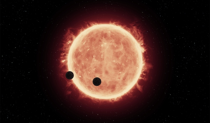 This illustration shows two Earth-sized worlds passing in front of their parent red dwarf star, which is much smaller and cooler than our sun. Credit: NASA/ESA/J. de Wit (MIT)/G. Bacon (STScI)