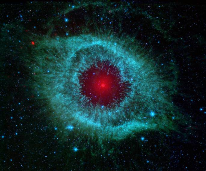 Dust makes this cosmic eye look red. This eerie Spitzer Space Telescope image shows infrared radiation from the well-studied Helix Nebula (NGC 7293), which is a mere 700 light-years away in the constellation Aquarius. The two light-year diameter shroud of dust and gas around a central white dwarf has long been considered an excellent example of a planetary nebula, representing the final stages in the evolution of a sun-like star. Spitzer data show the nebula's central star is itself immersed in a surprisingly bright infrared glow. Models suggest the glow is produced by a dust debris disk. Even though the nebular material was ejected from the star many thousands of years ago, the close-in dust could be generated by collisions in a reservoir of objects analogous to our own solar system's Kuiper Belt or cometary Oort cloud. Formed in the distant planetary system, the comet-like bodies have otherwise survived even the dramatic late stages of the star's evolution. Image credit: NASA, JPL-Caltech, Kate Su (Steward Obs, U. Arizona) et al.