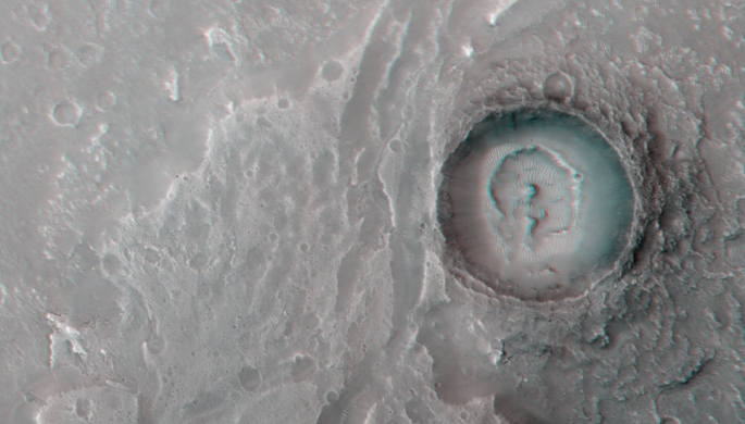 This image show a fan-shaped deposit where a channel enters a crater. This suggests that water once flowed through the channel into a crater lake, depositing material in a similar manner to river deltas on Earth. Credits: NASA/ESA/medialab