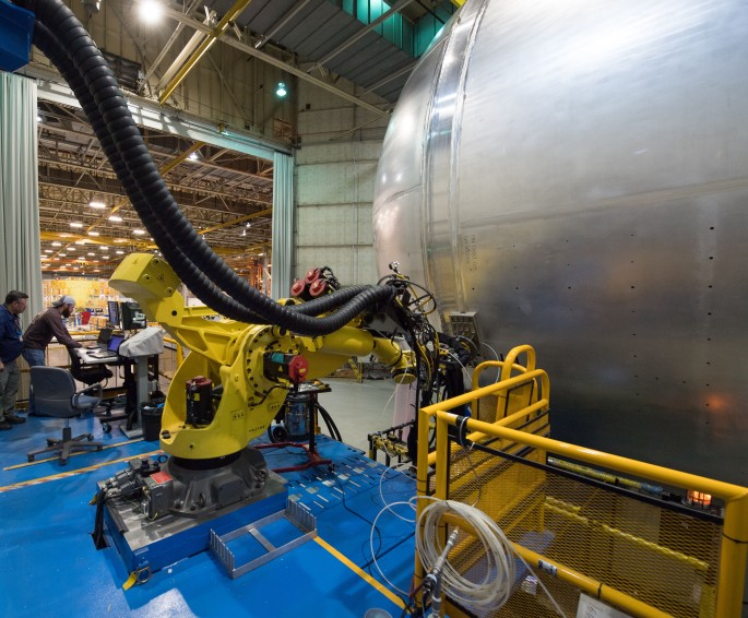 A team prepares a robot – the yellow machine attached to the liquid hydrogen tank for the Space Launch System rocket -- for friction plug welding at NASA's Michoud Assembly Facility in New Orleans. Friction plug welding is a technique developed by engineers at NASA's Marshall Space Flight Center in Huntsville, Alabama. It uses a robot to fill holes left after the tank goes through assembly in a larger robotic welder. The liquid hydrogen tank is more than 130 feet long and is the largest part of the rocket's core stage -- the backbone of the rocket. The liquid hydrogen tank, along with a liquid oxygen tank, will provide 733,000 gallons of fuel for the first integrated mission of SLS with NASA's Orion spacecraft in 2018. SLS will be the world's most powerful rocket and take astronauts in Orion to deep space, including on the Journey to Mars. Image Credit: NASA/Michoud/Steve Seipel
