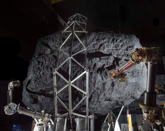 "A prototype of the Asteroid Redirect Mission (ARM) robotic capture module system is tested with a mock asteroid boulder in its clutches at NASA's Goddard Space Flight Center in Greenbelt, Maryland. The robotic portion of ARM is targeted for launch in 2021. Located in the center's Robotic Operations Center, the mockup helps engineers understand the intricate operations required to collect a multi-ton boulder from an asteroid's surface. The hardware involved here includes three space frame legs with foot pads, two seven degrees of freedom arms that have with microspine gripper ""hands"" to grasp onto the boulder. NASA and students from West Virginia University built the asteroid mockup from rock, styrofoam, plywood and an aluminum endoskeleton. The mock boulder arrived in four pieces and was assembled inside the ROC to help visualize the engagement between the prototype system and a potential capture target. Inside the ROC, engineers can use industrial robots, a motion-based platform, and customized algorithms to create simulations of space operations for robotic spacecraft. The ROC also allows engineers to simulate robotic satellite servicing operations, fine tuning systems and controllers and optimizing performance factors for future missions when a robotic spacecraft might be deployed to repair or refuel a satellite in orbit. Image Credit: NASA"
