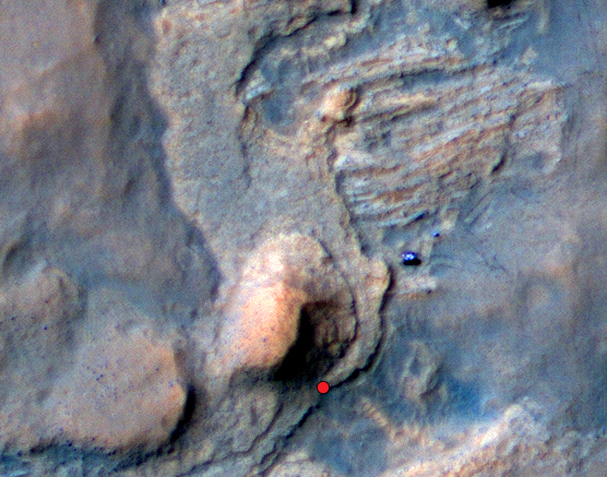 """On this view of the Curiosity rover mission's waypoint called """"the Kimberley,"""" the red dot indicates the location of a sandstone target, """"Windjana,"""" that researchers selected for close-up inspection and possibly for drilling. The view is an excerpt from an April 11, 2014, observation by the High Resolution Imaging Science Experiment (HiRISE) camera on NASA's Mars Reconnaissance Orbiter. A larger scene from the same observation is at http://photojournal.jpl.nasa.gov/catalog/PIA18081. In the image's enhanced color, Curiosity itself appears as the bright blue object at the two-o'clock position relative to the butte in the lower center of the scene. That butte is called """"Mount Remarkable"""" and stands about 16 feet (5 meters) high. The rover subsequently drove to within its robotic arm's reach of Windjana. For scale, the distance between the parallel wheel tracks visible in the image is about 9 feet (2.7 meters). In the area of the Kimberley waypoint, sandstone outcrops with differing resistance to wind erosion result in a stair-step pattern of layers. Windjana is within what the team calls the area's """"middle unit,"""" because it is intermediate between rocks that form buttes in the area and lower-lying rocks that show a pattern of striations. If Windjana meets criteria set by engineers and scientists, it could become the mission's third drilled rock and the first that is not mudstone. This view is an enhanced-color product from HiRISE observation ESP_036128_1755, available at the HiRISE website at http://uahirise.org/releases/msl-kimberley.php. The exaggerated color, to make differences in Mars surface materials more apparent, makes Curiosity appear bluer than the rover really looks. HiRISE is one of six instruments on NASA's Mars Reconnaissance Orbiter. The University of Arizona, Tucson, operates HiRISE, which was built by Ball Aerospace & Technologies Corp., Boulder, Colo. NASA's Jet Propulsion Laboratory, a division of the California Institute of Technology in Pasadena, """