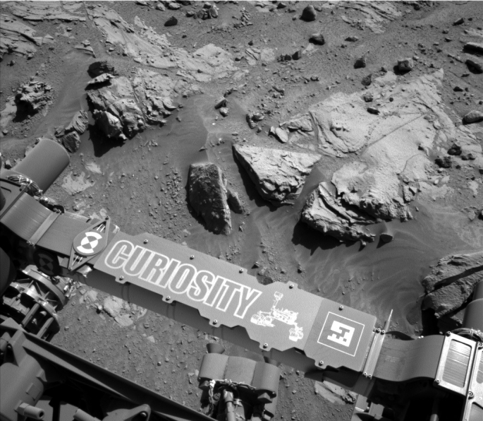 "This image from the Navigation Camera (Navcam) on NASA's Curiosity Mars rover shows a sandstone slab on which the rover team has selected a target, ""Windjana,"" for close-up examination and possible drilling. The target is on the approximately 2-foot-wide (60-centimeter-wide) rock seen in the right half of this view. The Navcam's left-eye camera took this image during the 609th Martian day, or sol, of Curiosity's work on Mars (April 23, 2014). The rover's name is written on the covering for a portion of the robotic arm, here seen stowed at the front of the vehicle. The sandstone target's informal name comes from Windjana Gorge in Western Australia. If this target meets criteria set by engineers and scientists, it could become the mission's third drilled rock and the first that is not mudstone. The rock is within a waypoint location called ""the Kimberley,"" where sandstone outcrops with differing resistance to wind erosion result in a stair-step pattern of layers. Windjana is within what the team calls the area's ""middle unit,"" because it is intermediate between rocks that form buttes in the area and lower-lying rocks that show a pattern of striations. NASA's Jet Propulsion Laboratory, a division of the California Institute of Technology, Pasadena, manages the Mars Science Laboratory Project for NASA's Science Mission Directorate, Washington. JPL designed and built the project's Curiosity rover and the rover's Navcam. > Read more: NASA's Curiosity Mars Rover Inspects Site Image Credit: NASA/JPL-Caltech"