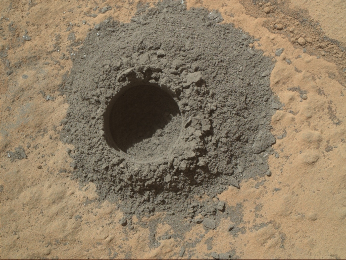 "NASA's Curiosity Mars rover completed a shallow ""mini drill"" activity on April 29, 2014, as part of evaluating a rock target called ""Windjana"" for possible full-depth drilling to collect powdered sample material from the rock's interior. This image from Curiosity's Mars Hand Lens Imager (MAHLI) instrument shows the hole and tailings resulting from the mini drill test. The hole is 0.63 inch (1.6 centimeters) in diameter and about 0.8 inch (2 centimeters) deep. When collecting sample material, the rover's hammering drill bores as deep as 2.5 inches (6.4 centimeters). This preparatory activity enables the rover team to evaluate interaction between the drill and this particular rock and to view the potential sample-collection target's interior and tailings. Both the mini drill activity and acquisition of this image occurred during the 615th Martian day, or sol, of Curiosity's work on Mars (April 29, 2014). MAHLI was built by Malin Space Science Systems, San Diego. NASA's Jet Propulsion Laboratory, a division of the California Institute of Technology in Pasadena, manages the Mars Science Laboratory Project for the NASA Science Mission Directorate, Washington. JPL designed and built the project's Curiosity rover. Credit: NASA/JPL-Caltech/MSSS"
