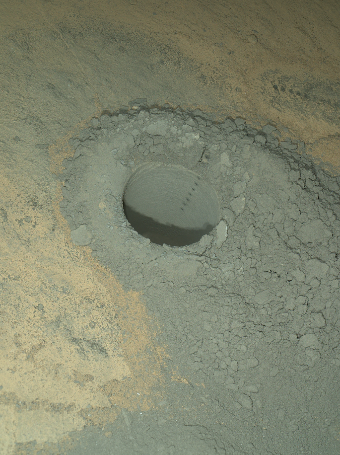 "NASA's Curiosity Mars rover used the Mars Hand Lens Imager (MAHLI) instrument on its robotic arm to illuminate and record this nighttime view of the sandstone rock target ""Windjana."" The rover had previously drilled a hole to collect sample material from the interior of the rock and then zapped a series of target points inside the hole with the laser of the rover's Chemistry and Camera (ChemCam) instrument. The hole is 0.63 inch (1.6 centimeters) in diameter. The precision pointing of the laser that is mounted atop the rover's remote-sensing mast is evident in the column of scars within the hole. That instrument provides information about the target's composition by analysis of the sparks of plasma generated by the energy of the laser beam striking the target. Additional ChemCam laser scars are visible at upper right, on the surface of the rock. This view combines eight separate MAHLI exposures, taken at different focus settings to show the entire scene in focus. The exposures were taken after dark on the 628th Martian day, or sol, of Curiosity's work on Mars (May 13, 2014). The rover drilled this hole on Sol 621 (May 5, 2014). MAHLI includes light-emitting diodes as well as a color camera. Using the instrument's own lighting yields an image of the hole's interior with less shadowing than would be seen in a sunlit image. The camera's inspection of the interior of the hole provides documentation about what the drill bit passed through as it penetrated the rock -- for example, to see if it cut through any mineral veins or visible layering. MAHLI was built by Malin Space Science Systems, San Diego. NASA's Jet Propulsion Laboratory, a division of the California Institute of Technology in Pasadena, manages the Mars Science Laboratory Project for the NASA Science Mission Directorate, Washington. JPL designed and built the project's Curiosity rover. Credit: NASA/JPL-Caltech/MSSS"