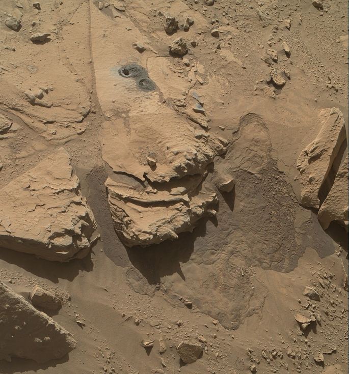 "This view from the Mars Hand Lens Imager (MAHLI) on NASA's Curiosity Mars Rover shows the rock target ""Windjana"" and its immediate surroundings after inspection of the site by the rover. The drilling of a test hole and a sample collection hole produced the mounds of drill cuttings that are markedly less red than the other visible surfaces. This is material that the drill pulled up from the interior of the rock. This view is from the 627th Martian day, or sol, of Curiosity's work on Mars (May 12, 2014). The open hole from sample collection is 0.63 inch (1.6 centimeters) in diameter. It was drilled on Sol 621 (May 5, 2014). A preparatory ""mini drill"" hole, to lower right from the open hole, was drilled on Sol 615 (April 29, 2014) and subsequently filled in with cuttings from the sample collection drilling. Two small patches of less-red color to the right of the drill holes are targets ""Stephen"" (higher) and ""Neil,"" where multiple laser hits by Curiosity's Chemistry and Camera (ChemCam) instrument blasted some of the reddish surface dust off the surface of the rock. The vigorous activity of penetrating the rock with the rover's hammering drill also resulted in slides of loose material near the rock. For comparison to the site before the drilling, see the Sol 609 image of Windjana at http://photojournal.jpl.nasa.gov/catalog/PIA18087. MAHLI was built by Malin Space Science Systems, San Diego. NASA's Jet Propulsion Laboratory, a division of the California Institute of Technology in Pasadena, manages the Mars Science Laboratory Project for the NASA Science Mission Directorate, Washington. JPL designed and built the project's Curiosity rover. Credit: NASA/JPL-Caltech/MSSS"