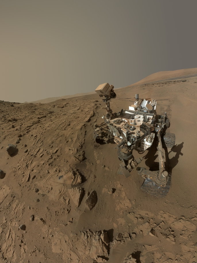 "NASA's Curiosity Mars rover used the camera at the end of its arm in April and May 2014 to take dozens of component images combined into this self-portrait where the rover drilled into a sandstone target called ""Windjana."" The camera is the Mars Hand Lens Imager (MAHLI), which previously recorded portraits of Curiosity at two other important sites during the mission: ""Rock Nest"" (http://photojournal.jpl.nasa.gov/catalog/PIA16468) and ""John Klein"" (http://photojournal.jpl.nasa.gov/catalog/PIA16937). Winjana is within a science waypoint site called ""The Kimberley,"" where sandstone layers with different degrees of resistance to wind erosion are exposed close together. The view does not include the rover's arm. It does include the hole in Windjana produced by the hammering drill on Curiosity's arm collecting a sample of rock powder from the interior of the rock. The hole is surrounded by grayish cuttings on top of the rock ledge to the left of the rover. The Mast Camera (Mastcam) atop the rover's remote sensing mast is pointed at the drill hole. A Mastcam image of the drill hole from that perspective is at http://mars.jpl.nasa.gov/msl/multimedia/raw/?rawid=0626MR0026780000401608E01_DXXX&s=626. The hole is 0.63 inch (1.6 centimeters) in diameter. The rover's wheels are 20 inches (0.5 meter) in diameter. Most of the component frames of this mosaic view were taken during the 613th Martian day, or sol, of Curiosity's work on Mars (April 27, 2014). Frames showing Windjana after completion of the drilling were taken on Sol 627 (May 12, 2014). The hole was drilled on Sol 621 (May 5, 2014). MAHLI was built by Malin Space Science Systems, San Diego. NASA's Jet Propulsion Laboratory, a division of the California Institute of Technology in Pasadena, manages the Mars Science Laboratory Project for the NASA Science Mission Directorate, Washington. JPL designed and built the project's Curiosity rover. > NASA's Mars Curiosity Rover Marks First Martian Year with Mission Successes Image Credit: NASA/JPL-Caltech/MSSS"